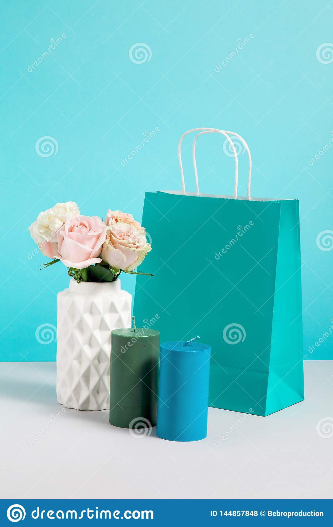 Still life image with flower in vase, candle and paper bag. Mockup of craft shopping bags. Concept for sales or discounts.