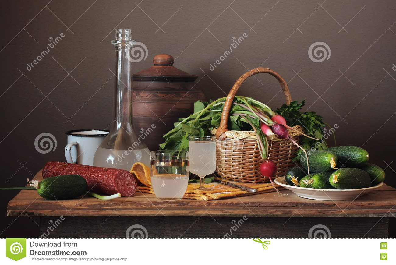 Still life with moonshine, fresh vegetables and sausage.