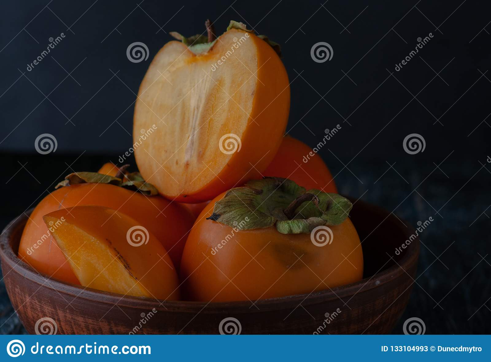 Still life with persimmon on a plate on a dark background.