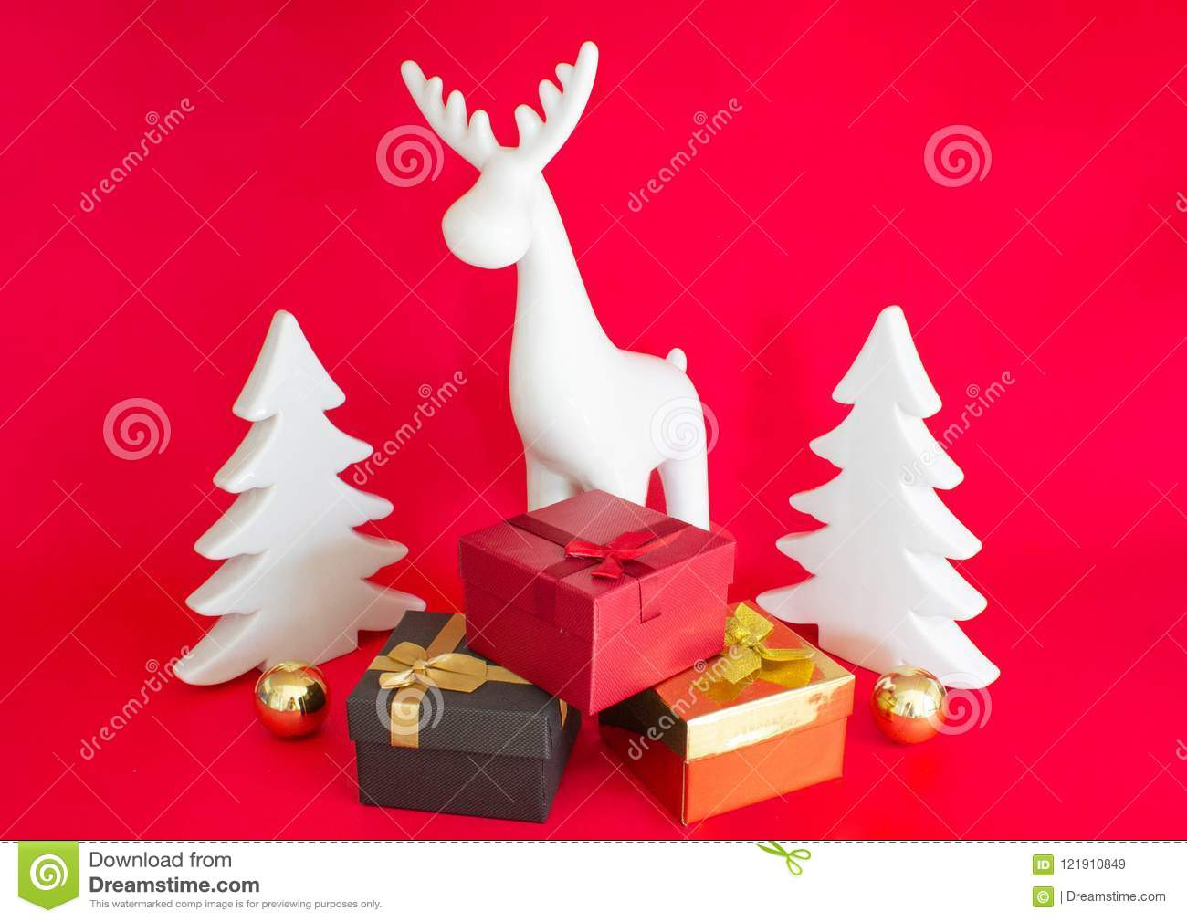 still life on a red background gift boxes white deer and christmas tree