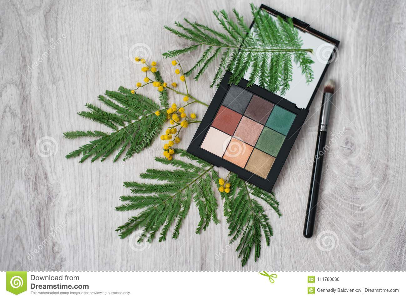 Still life of summer cosmetic make-up, brush and flowers of mimosa on a wooden table. Decor and makeup