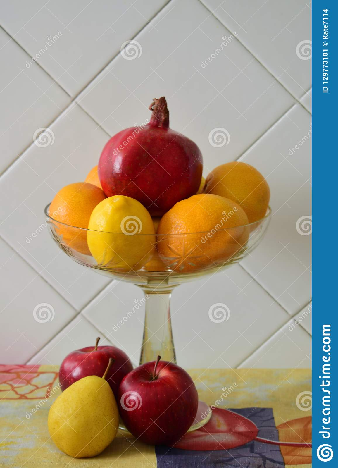 Still life in a transparent glass vase with red pomegranate, tangerines, lemon and apple
