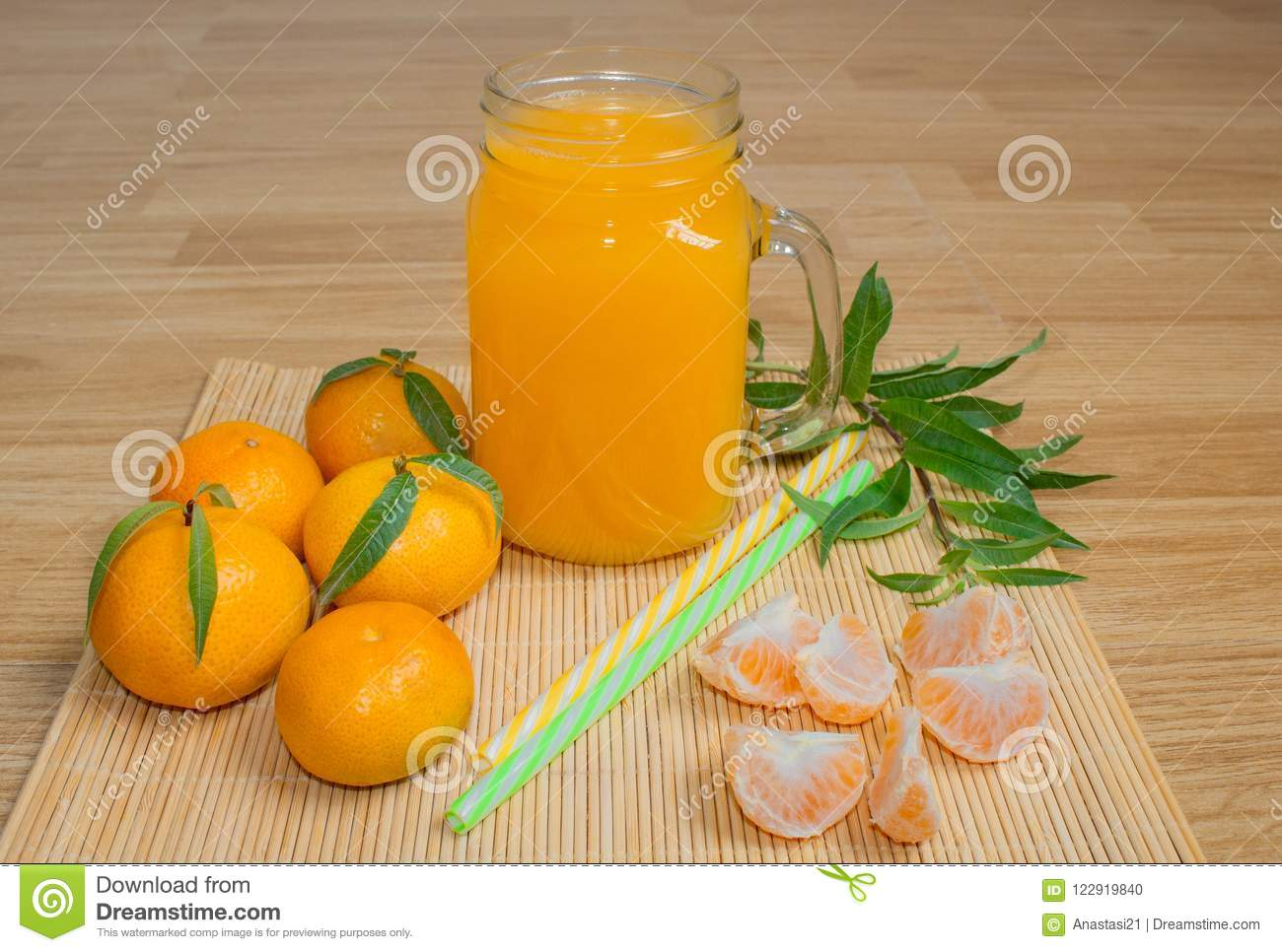 Still life. A transparent mug with a handle with freshly squeezed tangerine juice. And fresh tangerines.
