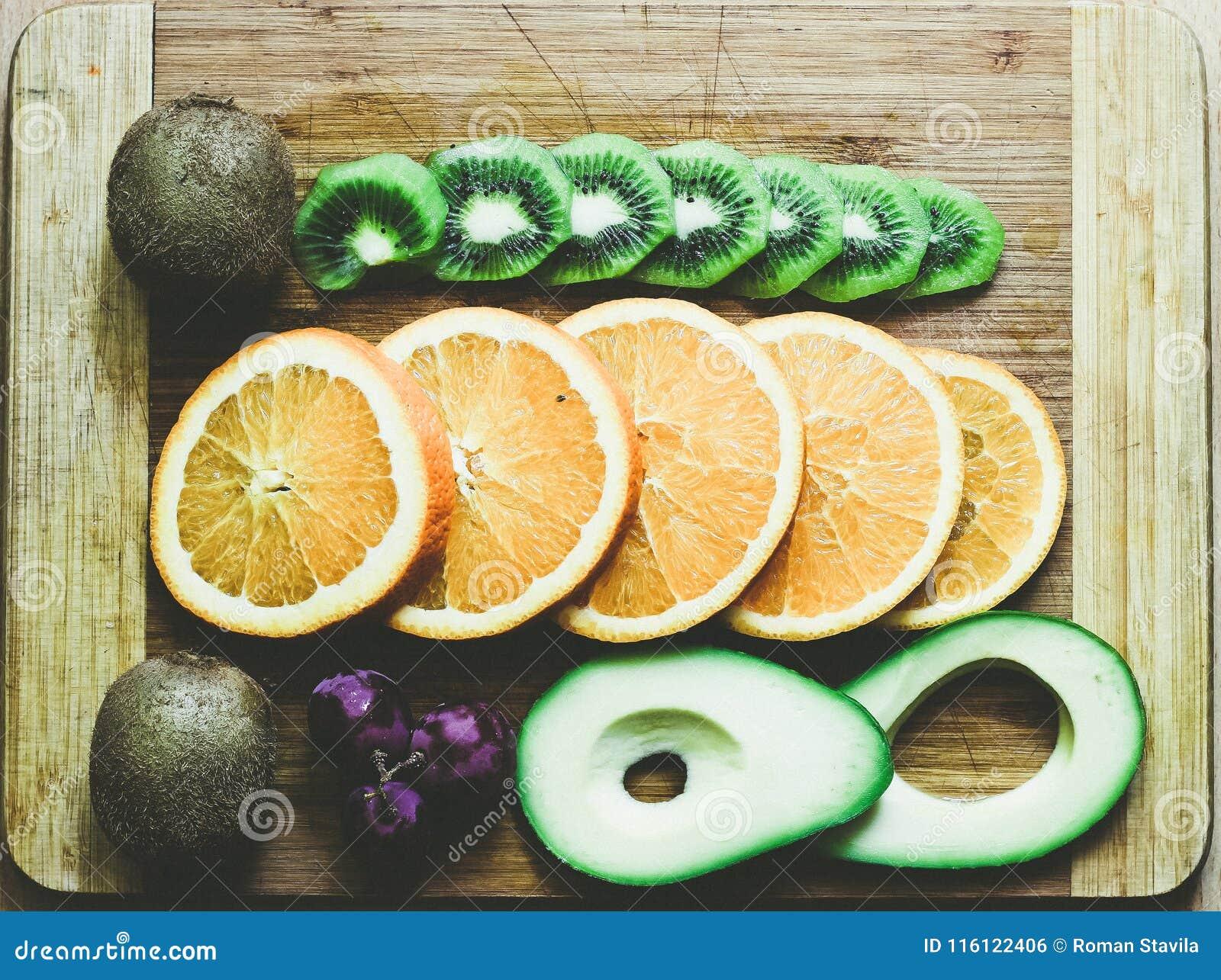 Stilleben av avokadot, druvor, apelsinen och kiwin