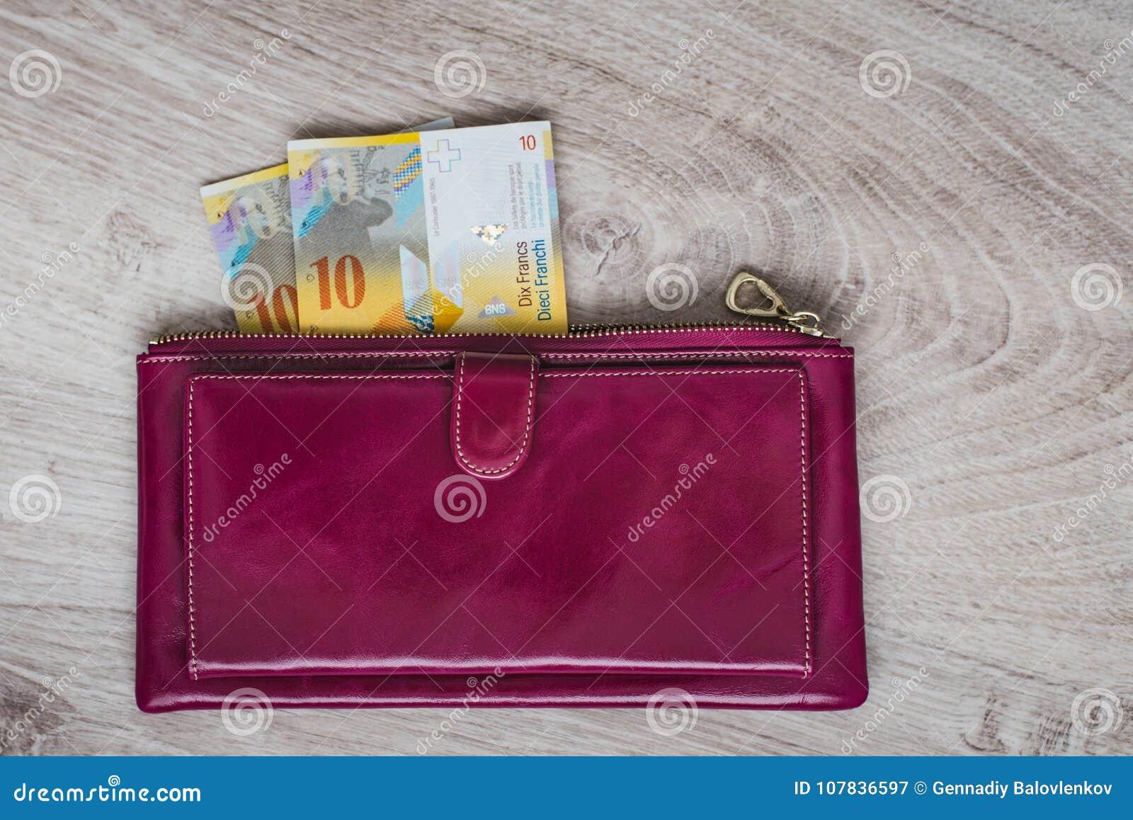 Stilleben av kassa Bordeaux läderplånbok och schweizisk franc på en träbakgrund