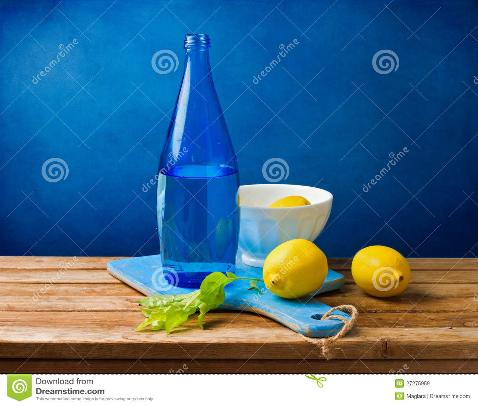 Stilleben med citroner och den blåa flaskan