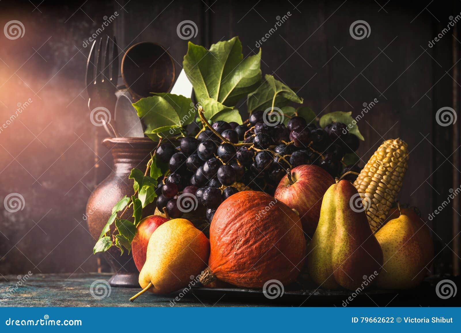 Stilleben med höstfrukter och grönsaker: äpplen päron, druvor, pumpor, havre på majskolven på det mörka lantliga köksbordet