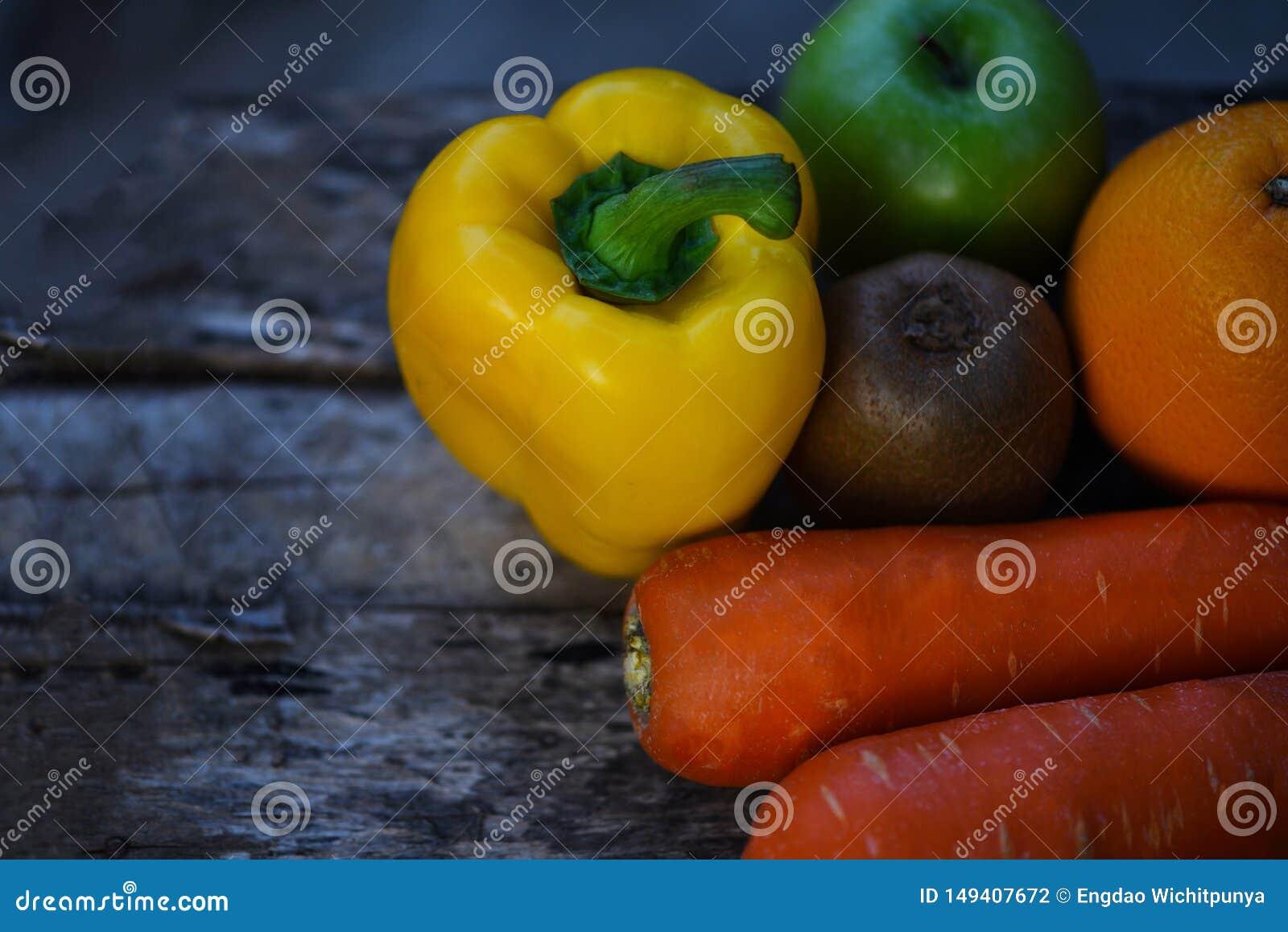 Stillebenfrukt med f?r ?pplemorot f?r gul spansk peppar den gr?na apelsinen och kiwin p? lantligt tr?