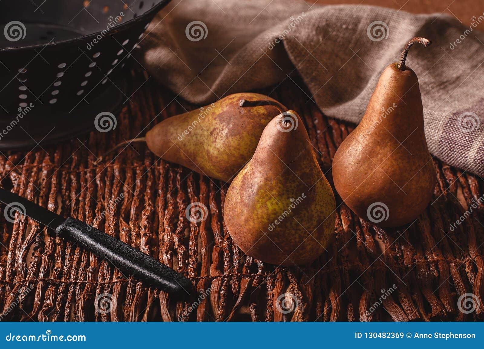 Stillebenplatsen av tre päron, den vävde en skala kniv, durkslaget och handduken på fattar bakgrund