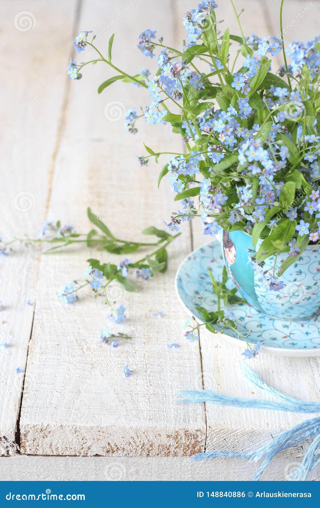 Stilleven met uiterst kleine de lentebloemen in een blauwe kop