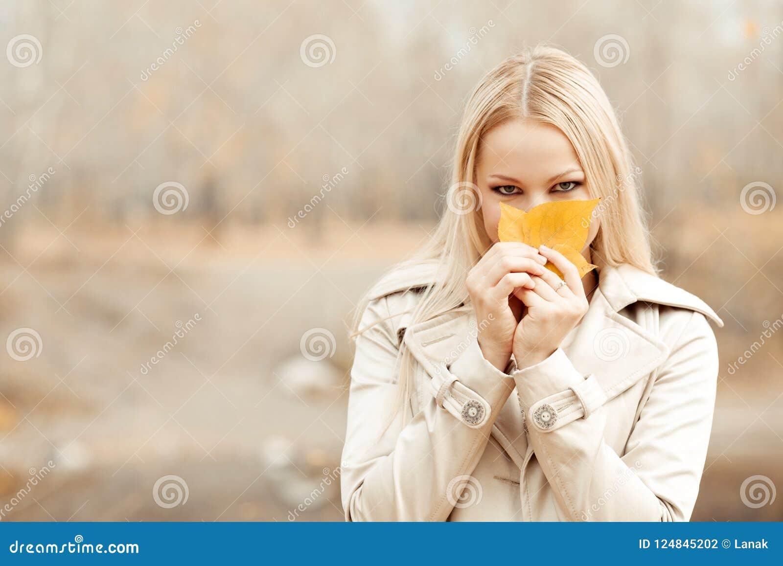 Stilvolle blonde Frau im Herbstpark