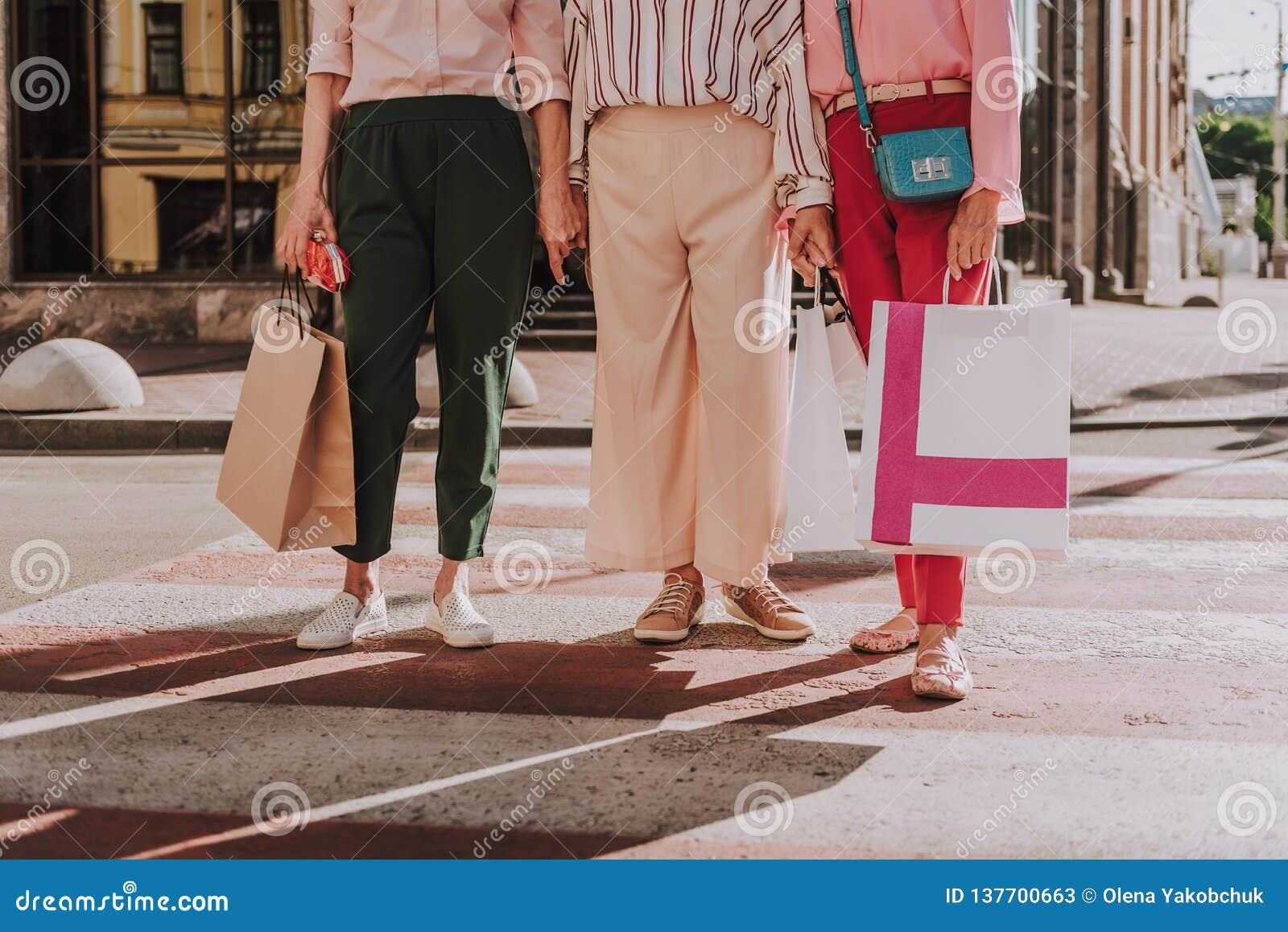 Stilvolle Frauen halten Einkaufstaschen im Freien