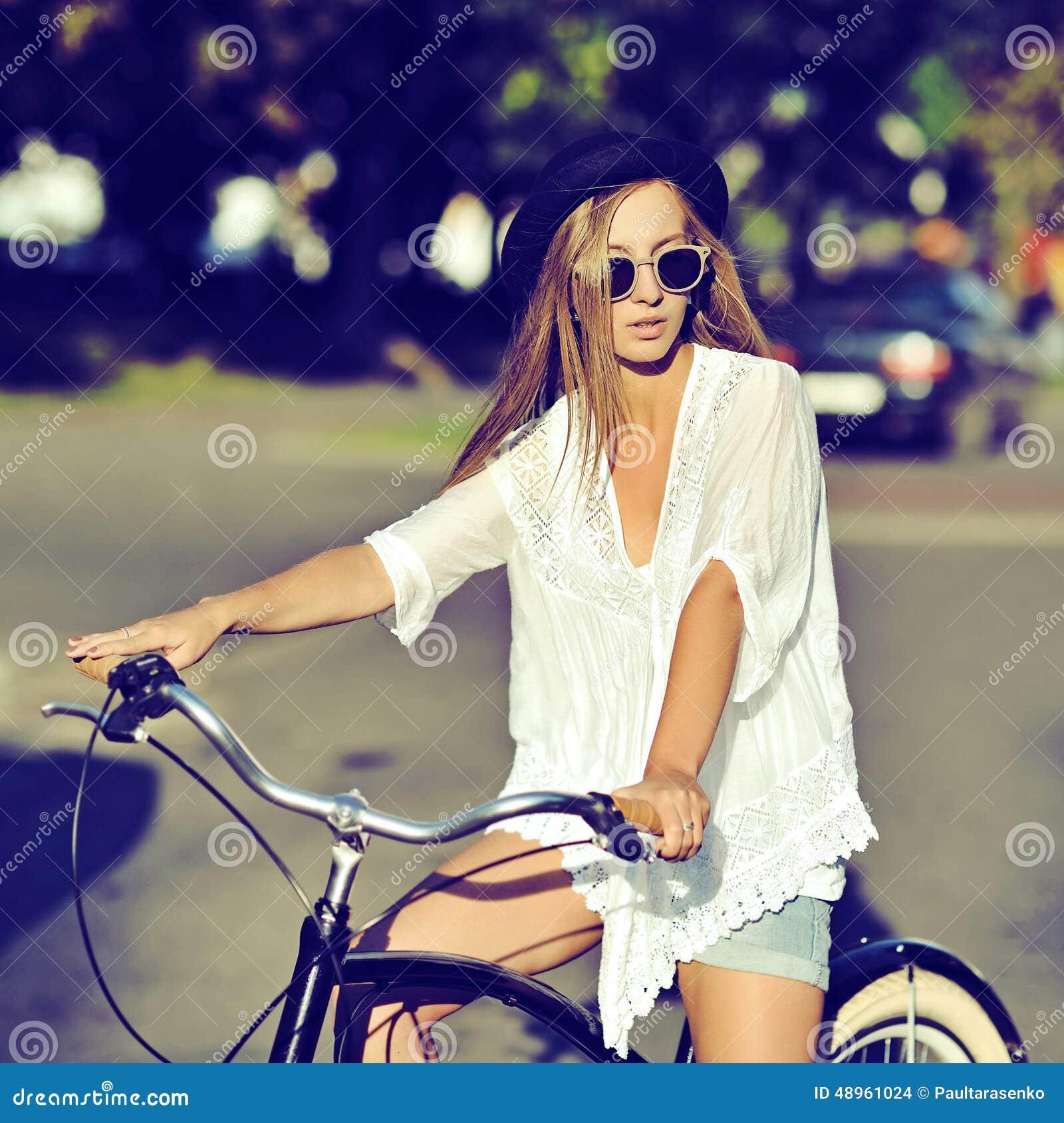 Stilvolle junge Hippie-Frau auf einem Retro- Fahrrad Im Freienart und weise