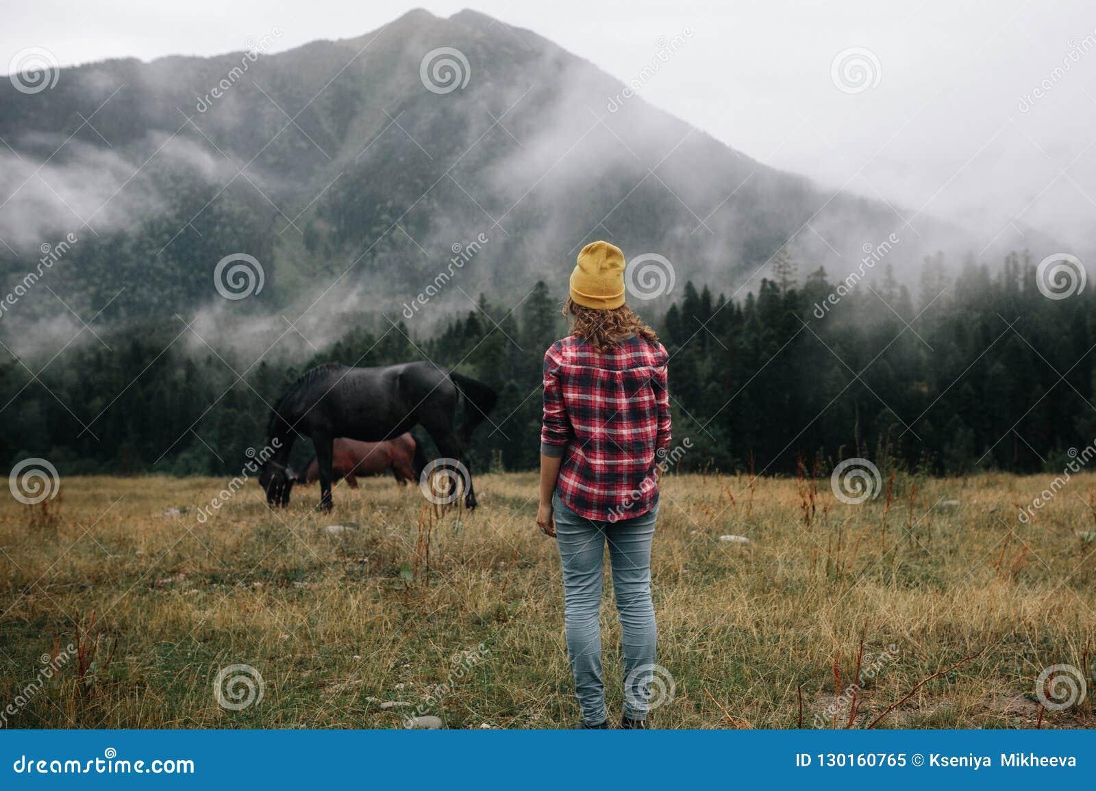 Stilvoller Mädchenblick auf das Pferd über Bergen im Nebel