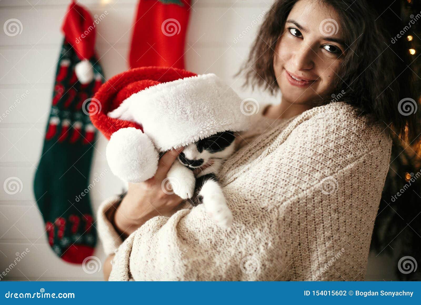 Stilvolles glückliches Mädchen, das mit netter Katze in Sankt-Hut im Hintergrund von Weihnachtsbaumlichtern und -strümpfen lächel