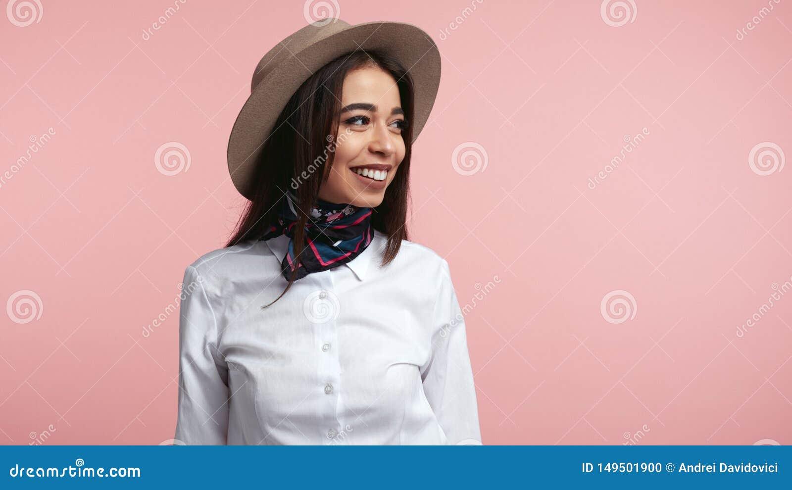 Stilvolles junges M?dchen, lacht gl?cklich, dr?ckt aufrichtige Gef?hle, tragendes wei?es Hemd und Hut, ?ber Rosa aus