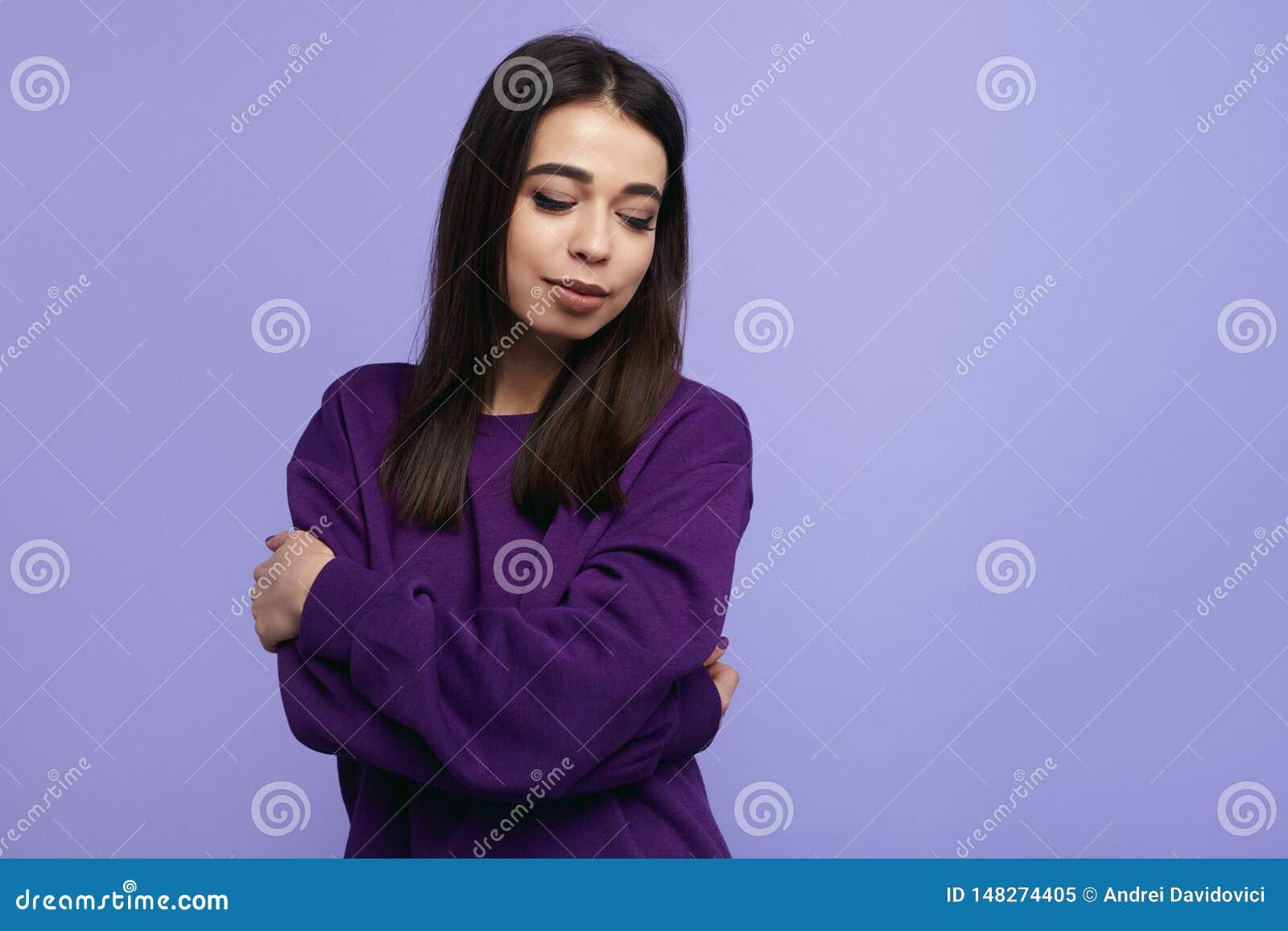 Stilvolles junges Mädchen mit geschlossenen Augen, die tragende purpurrote Strickjacke, die Arme halten kreuzte während Stellung