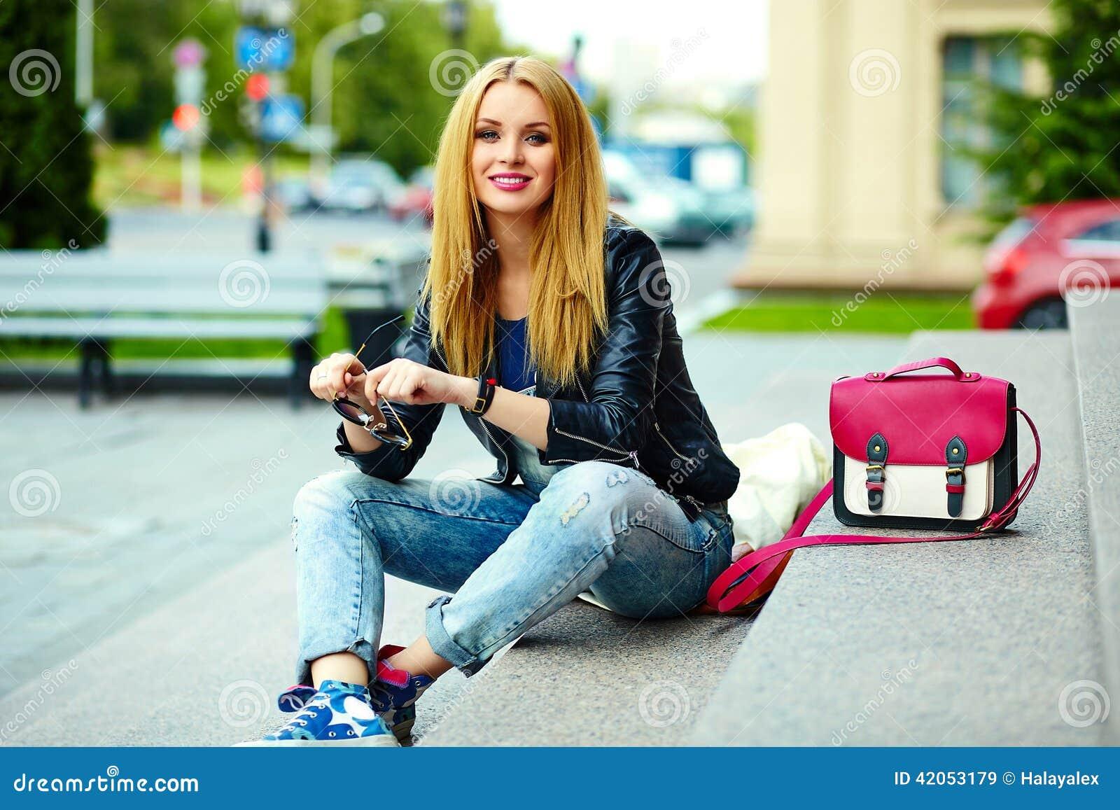 Stilvolles lächelndes Mädchen im zufälligen Stoff im Stadtpark