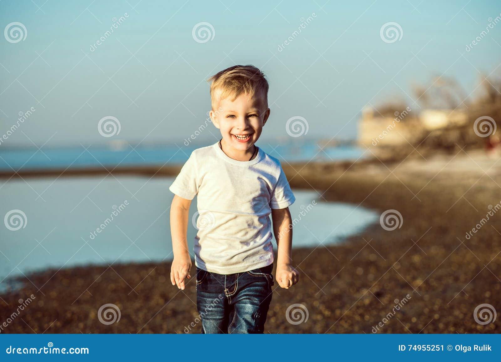 Stilvolles lachendes Kind, das entlang die Küste läuft