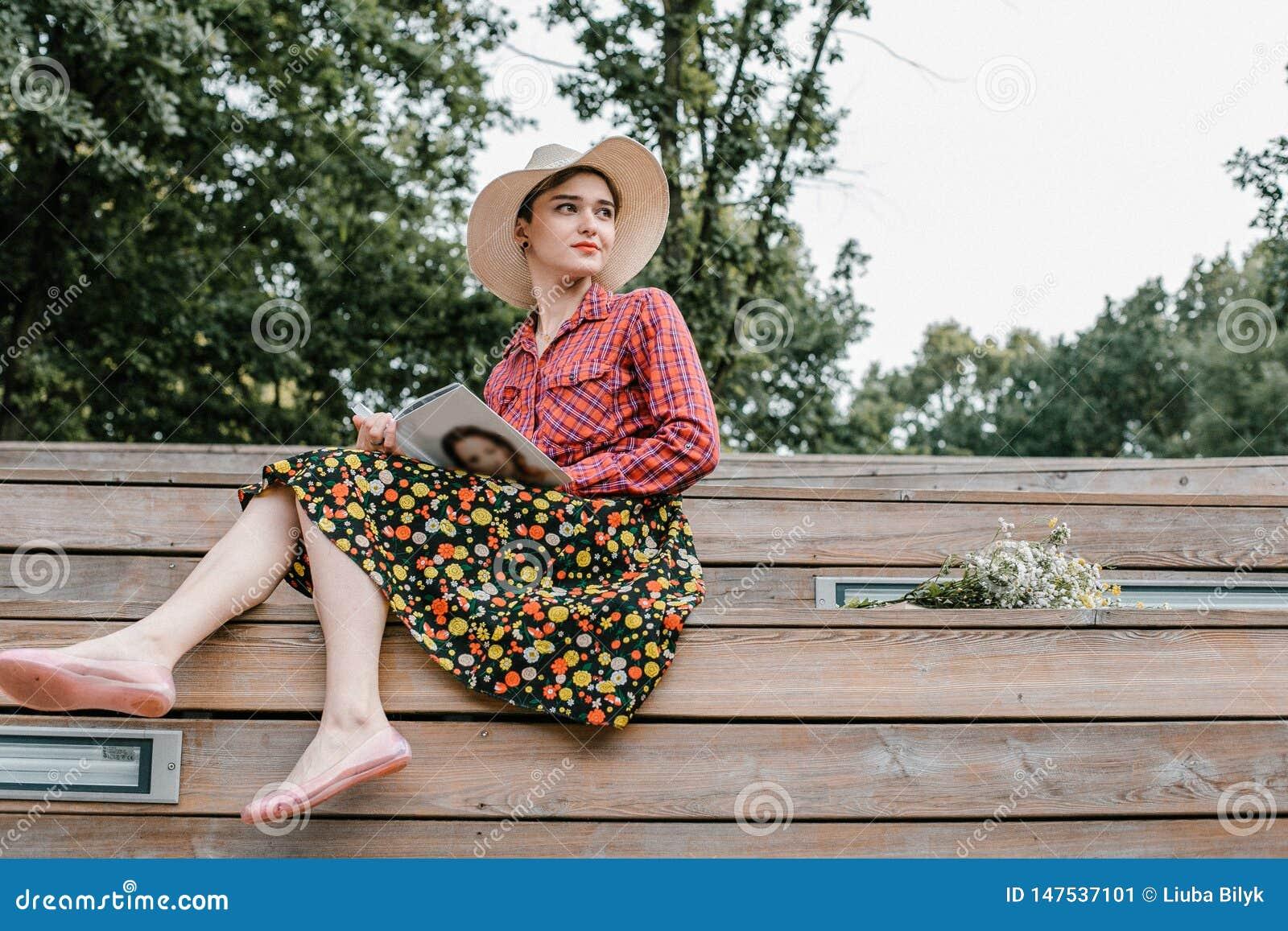 Stilvolles Mädchen, das ein Buch liest Eine Schönheit mit einem Hut, der auf Treppe eines Baums sitzt Ein Student liest ein Buch