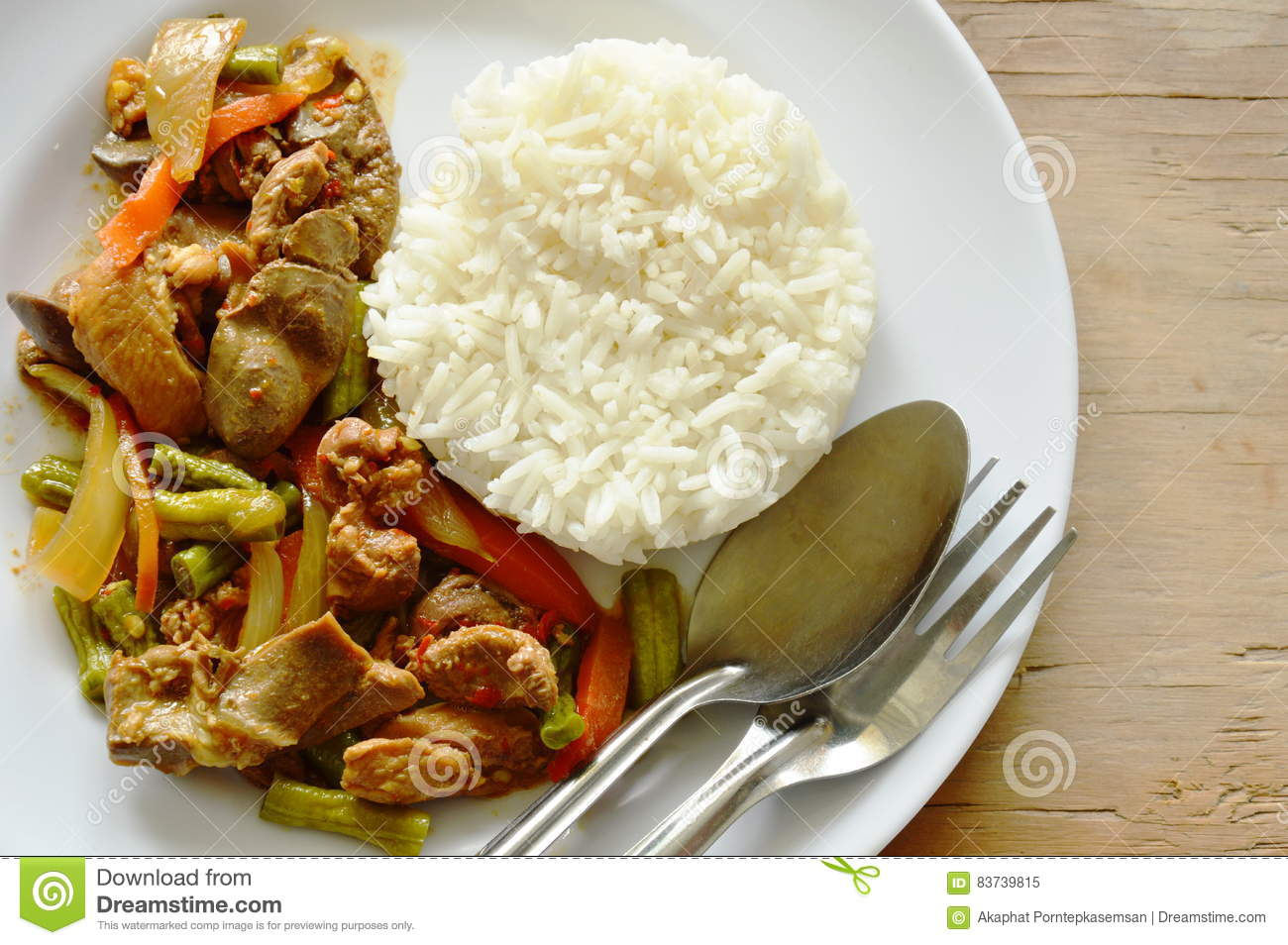 Stir fried chicken and mixed entrails with sweet chili eat couple with rice on plate