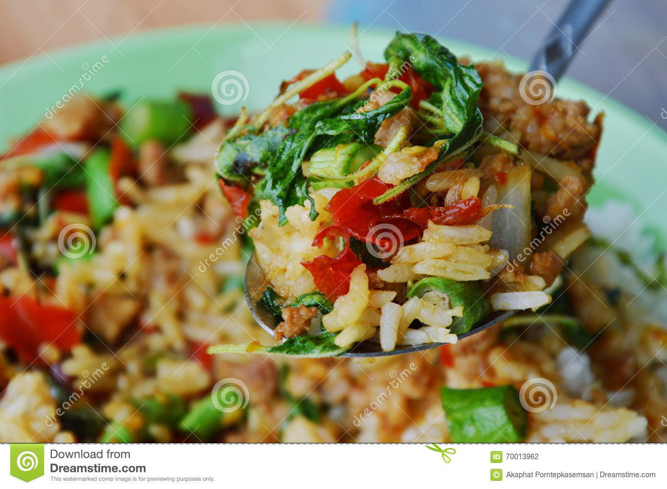 Stir-fried spicy minced pork with basil leaf and rice on spoon