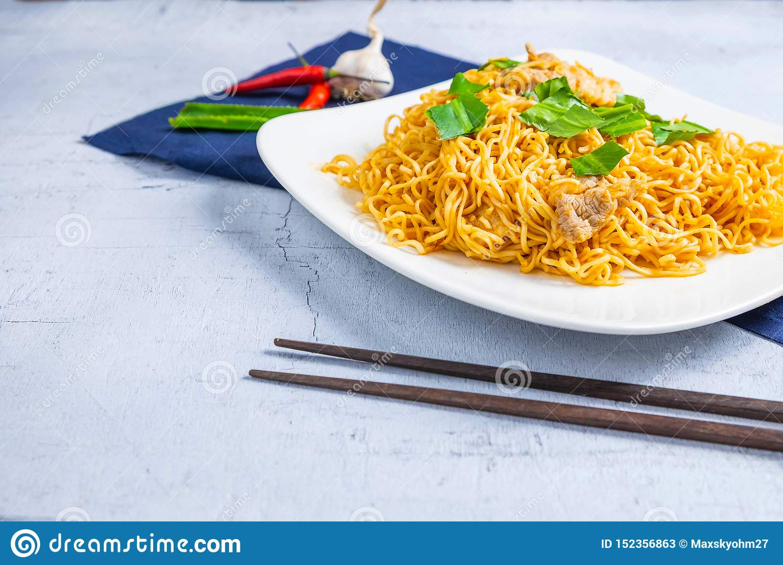 Stir noodles with vegetables in a white plate on a wooden floor