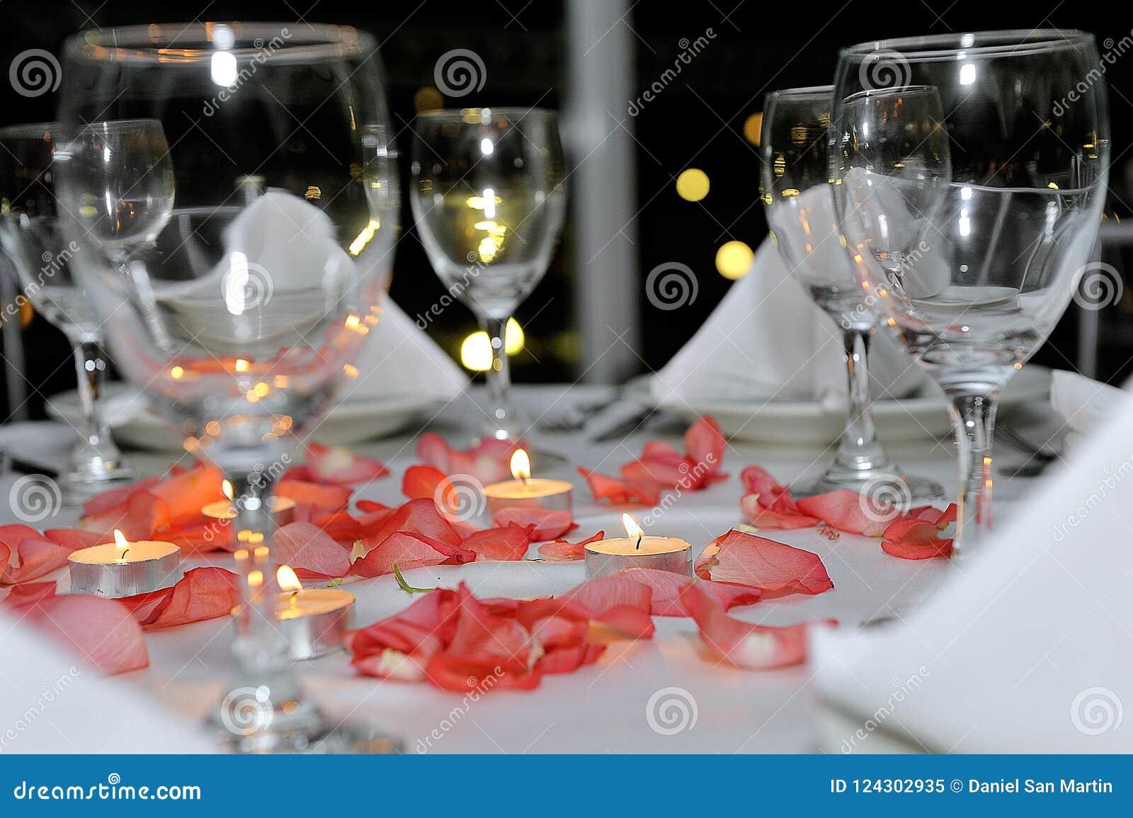 Stołowy położenie wystrój z cutlery, talerzami i szkłami dekorującymi z bukietem, peonie, różani płatki i świeczki, dalej