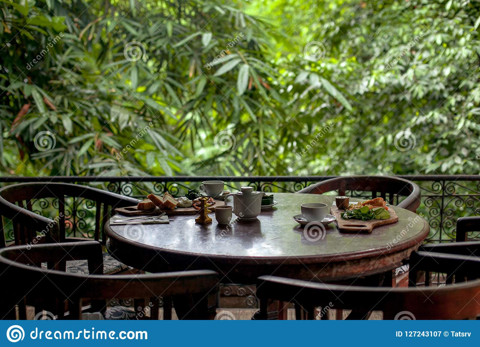 Stołu set dla śniadania przy wygodną restauracją na greenery tarasie w Bali stylu