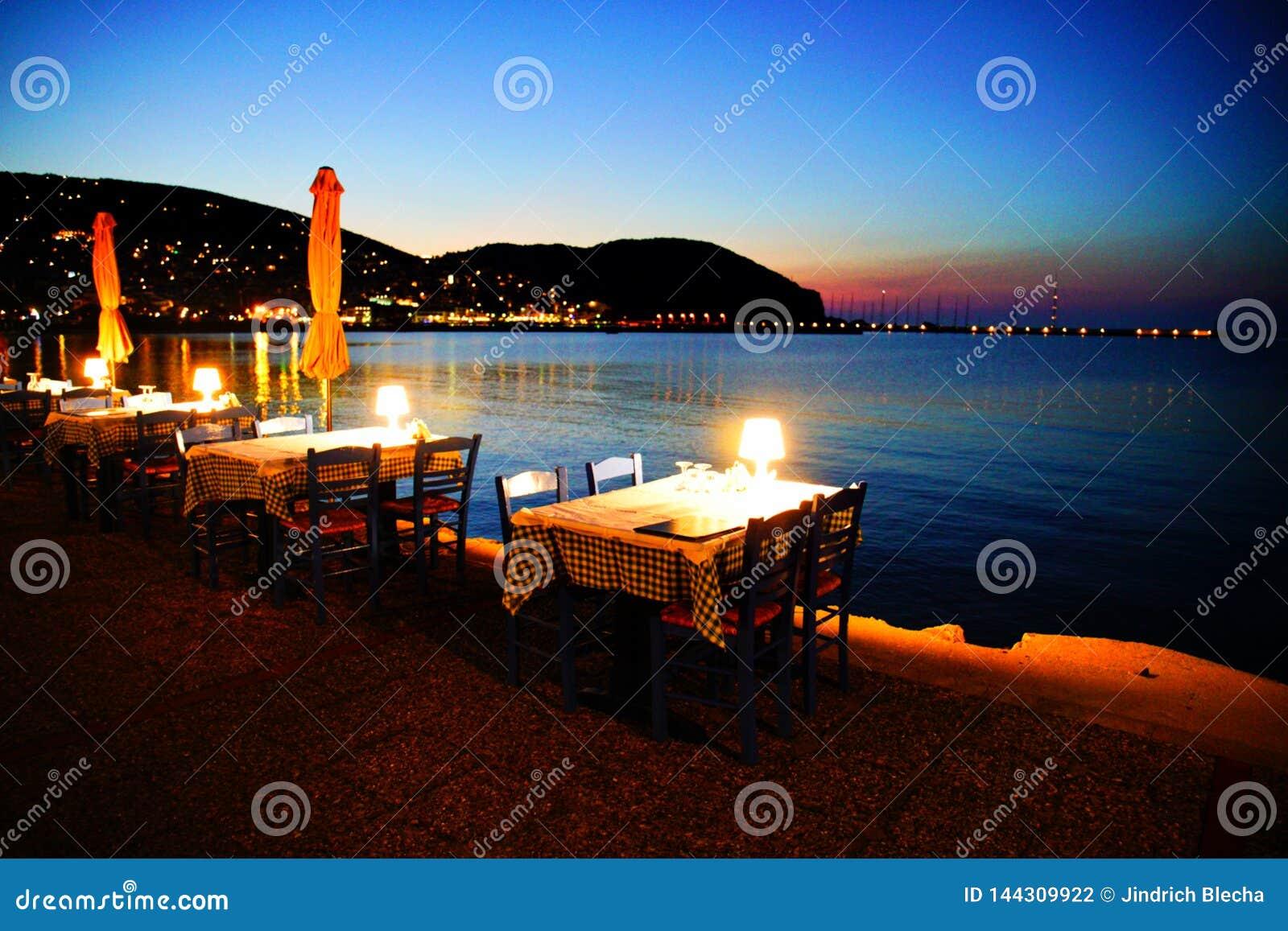 Stoły na plażowym deptaku w Skopelos miasteczku przy zmierzchem