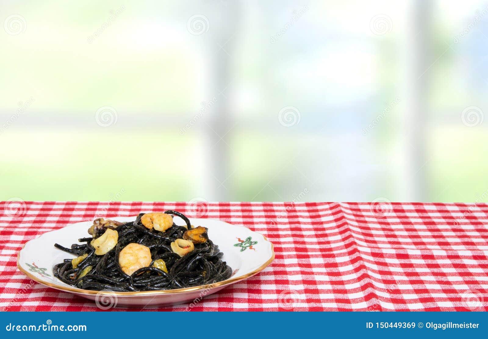 Sto?owy wierzcho?ek na owoce morza tle Zbli?enie ?r?dziemnomorscy czarni kluski z atramentem, mussels i garnelami na czerwieni cu