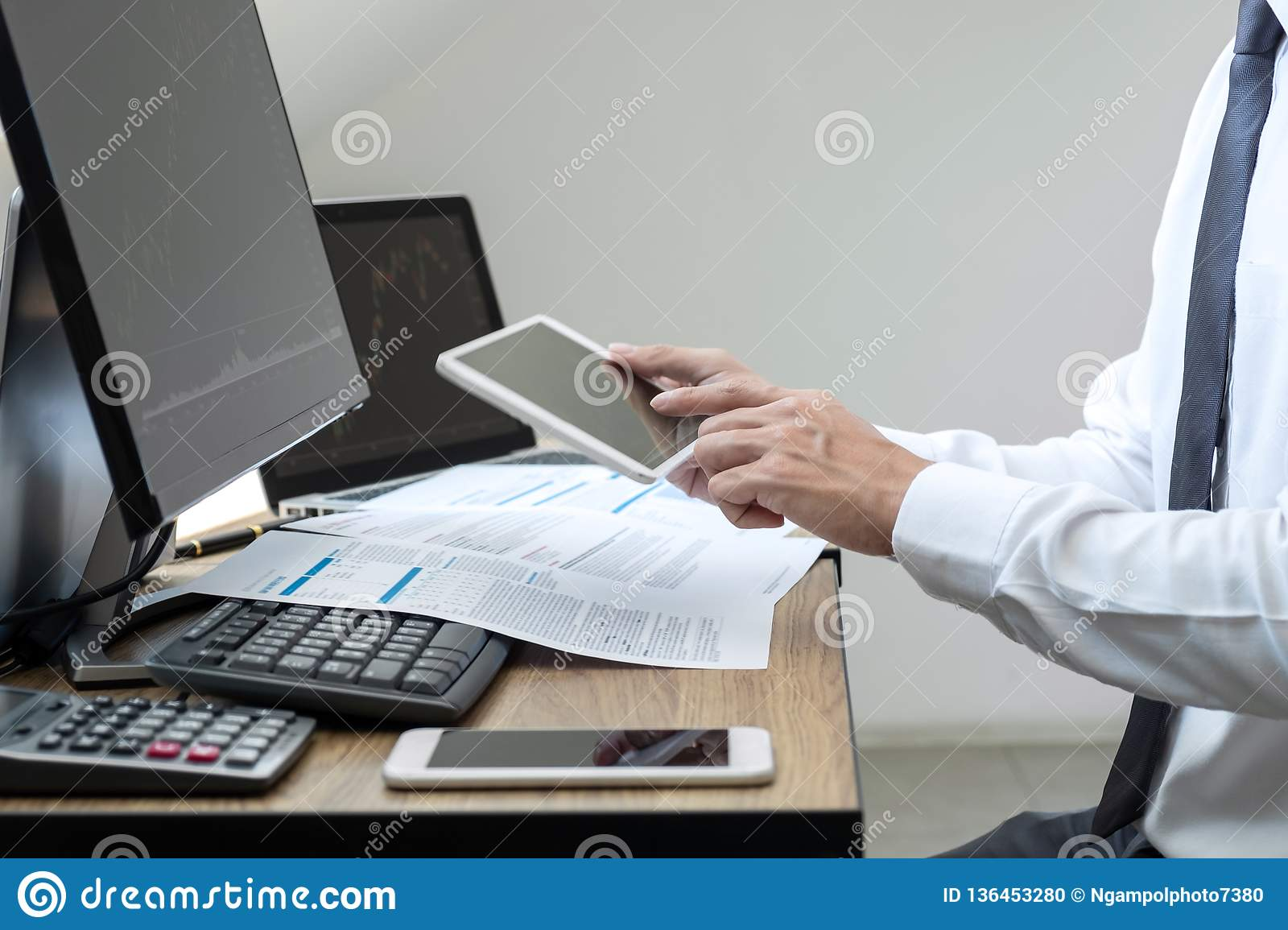 Stock exchange market concept, stock broker looking at graph working and analyzing with display screen, pointing on the data