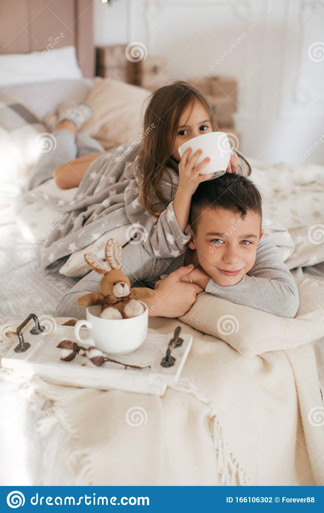 Eautiful Little Girl And Boy Are On The Bed In Bedroom With Christmas Decoration Stock Photo Image Of Love Chair 166106302