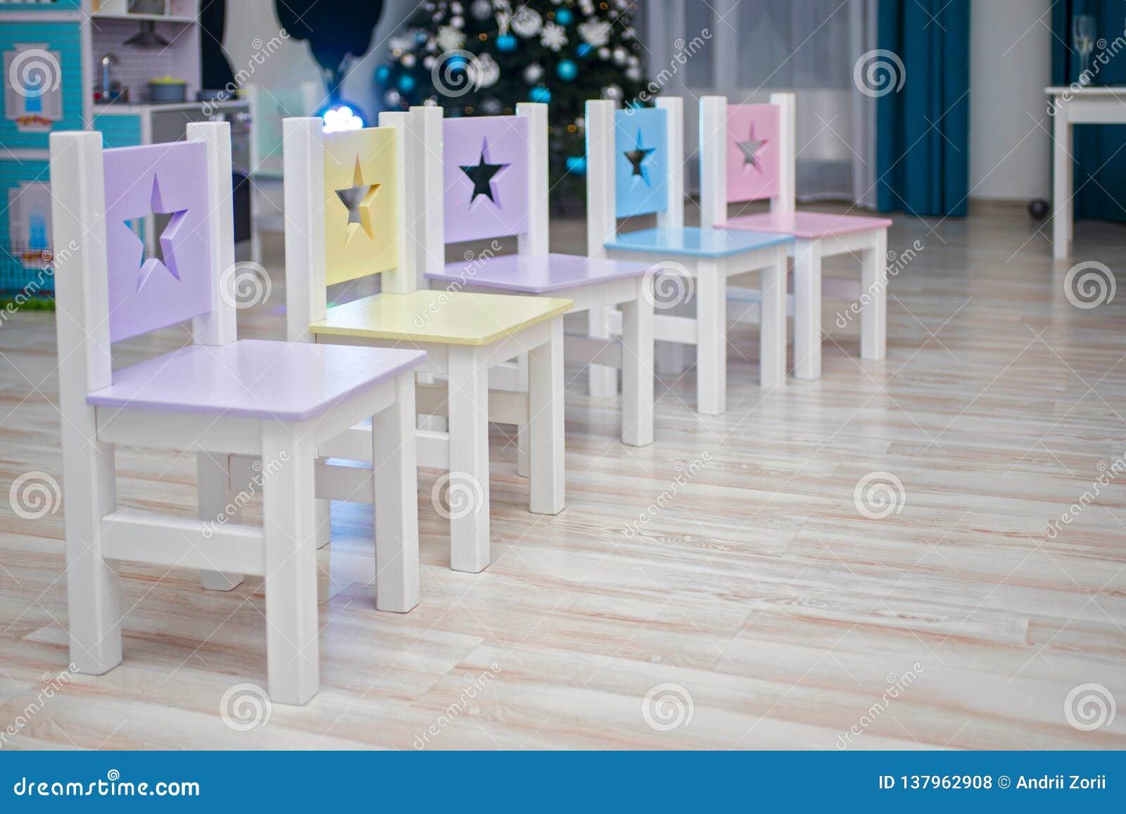 Stoelen in de ruimte van kinderen Het binnenland van de jonge geitjesruimte Stoelen in kleuterschool peuterklaslokaal Vele helder