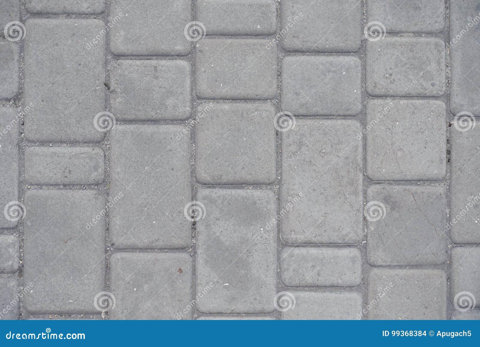 Stoffige grijze die bestrating van concrete blokken wordt gemaakt