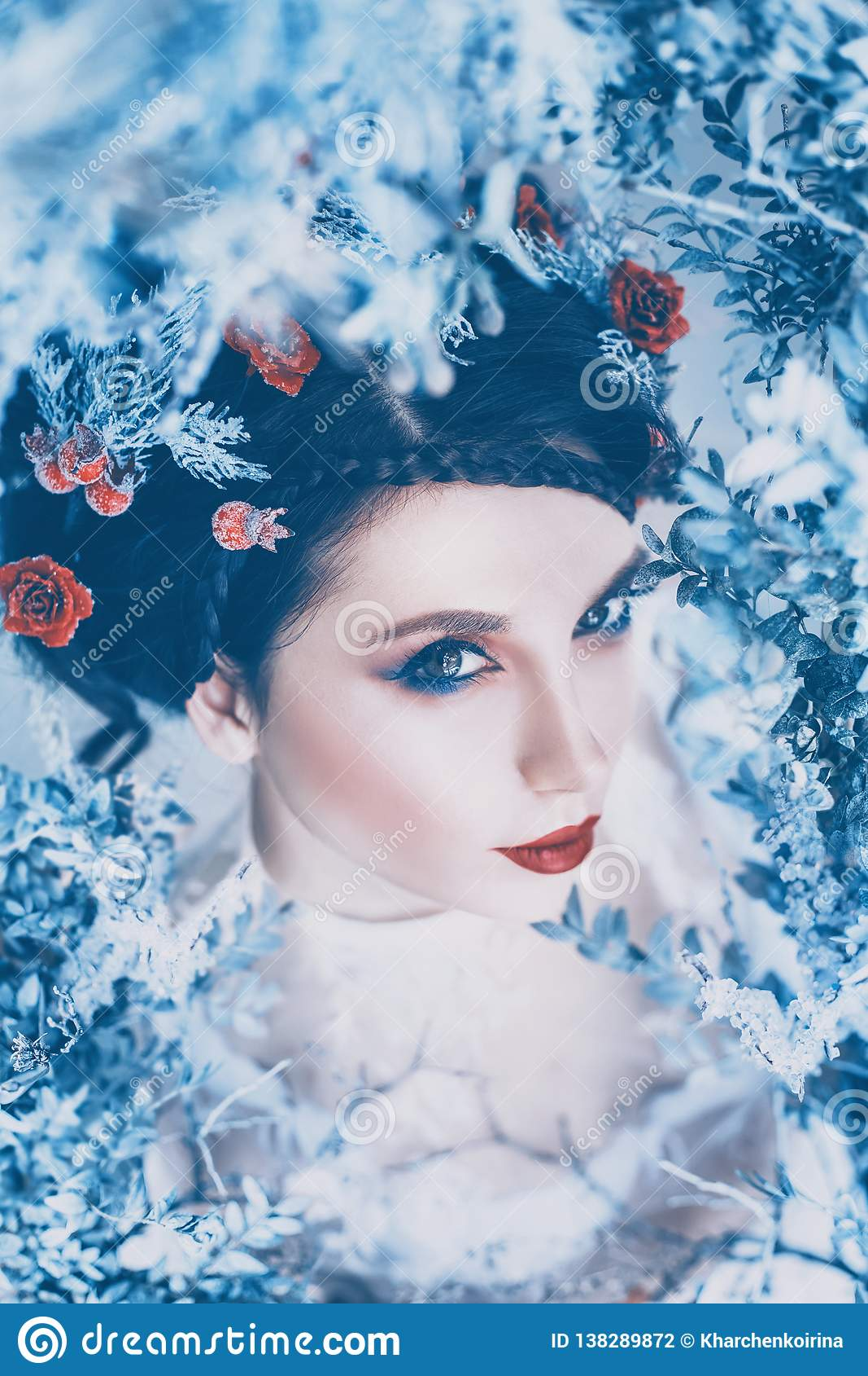 Stolt majestätisk drottning av vintern och evig förkylning i lång vit klänning med mörkt samlat hår som smyckas med djupfrysta ro