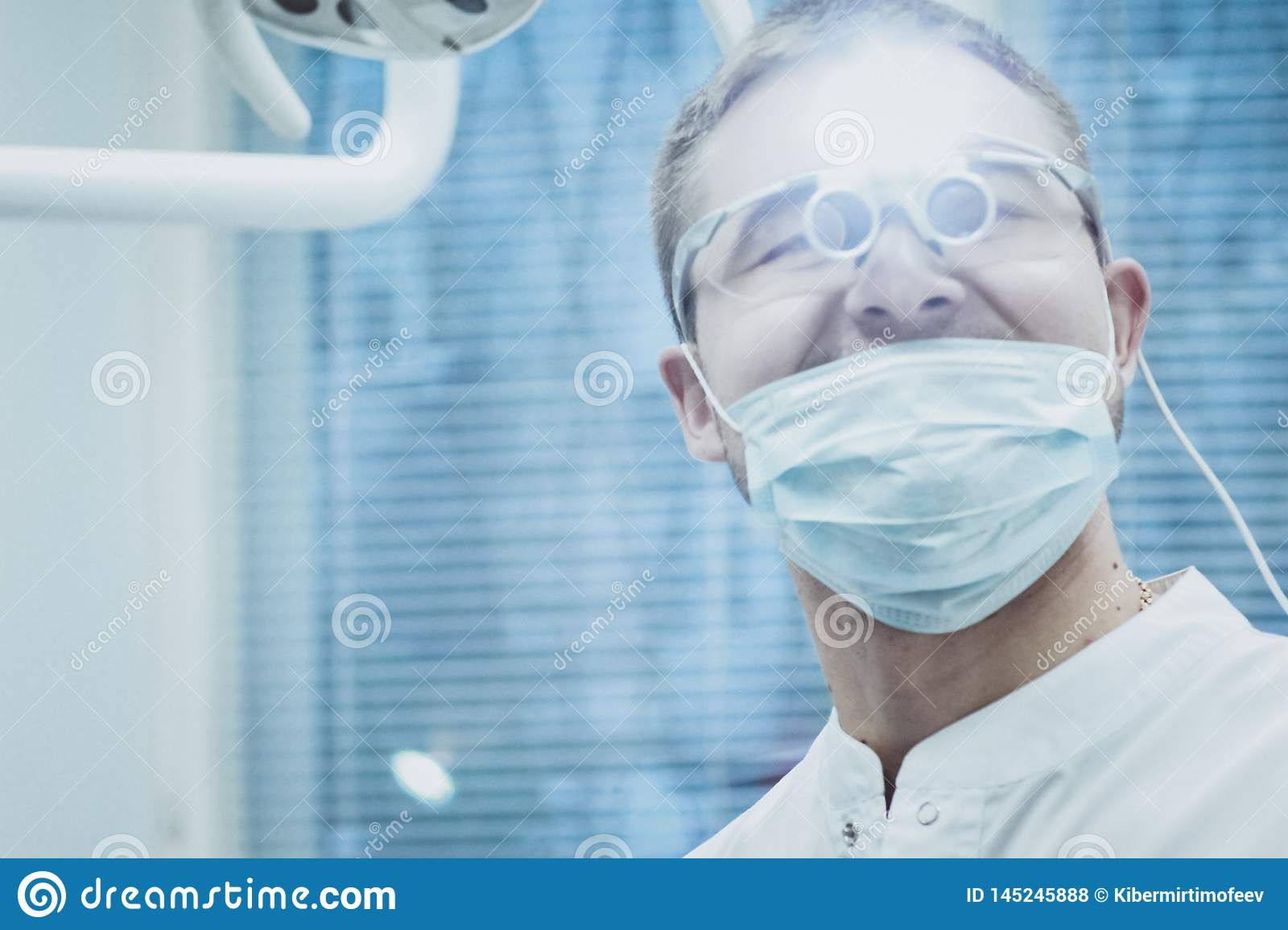 Stomatology. Dentist doctor shines in the eyes of a special device