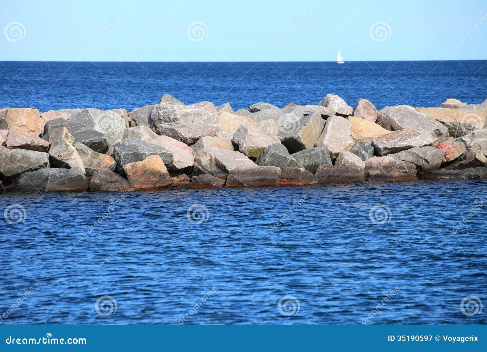 Granite Block Seawall : Stone breakwater for protection of coast royalty free
