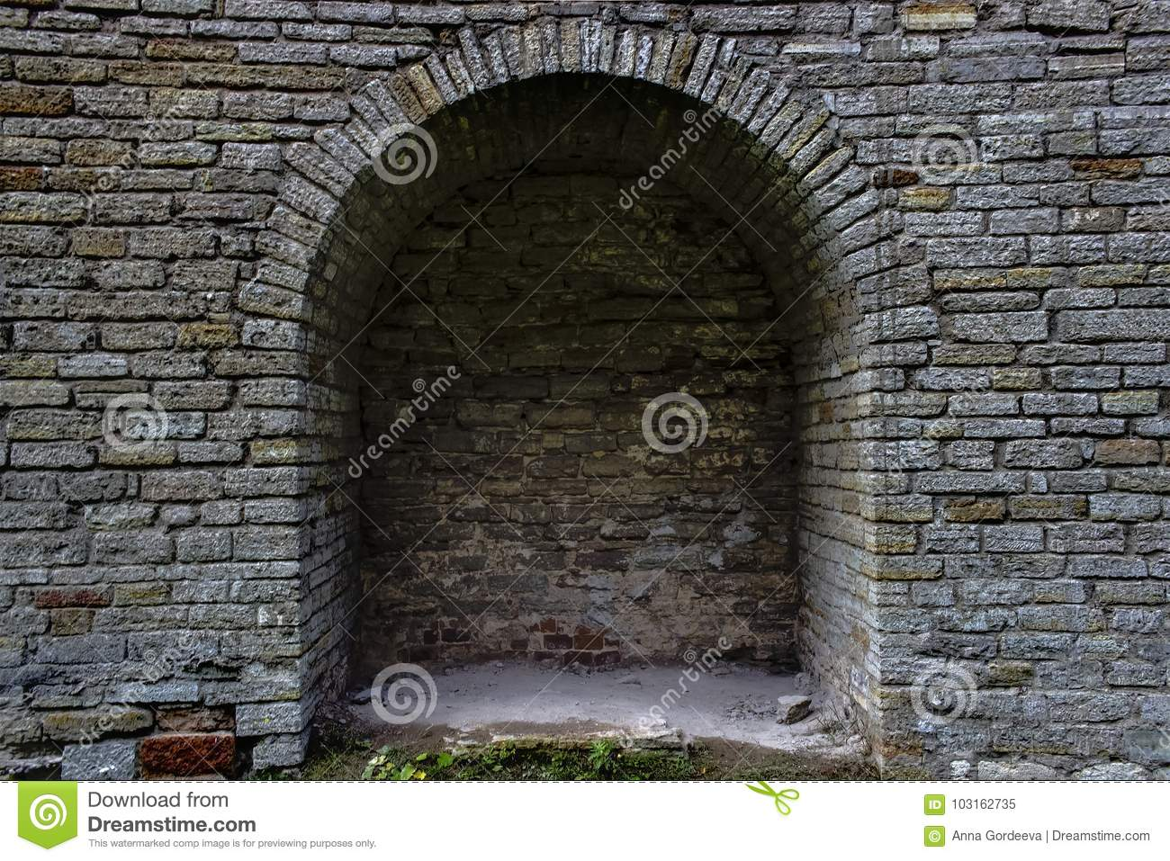 Stone brick antique arch is a window. Northern Europe, the castle. Fortress wall made of gray bricks.