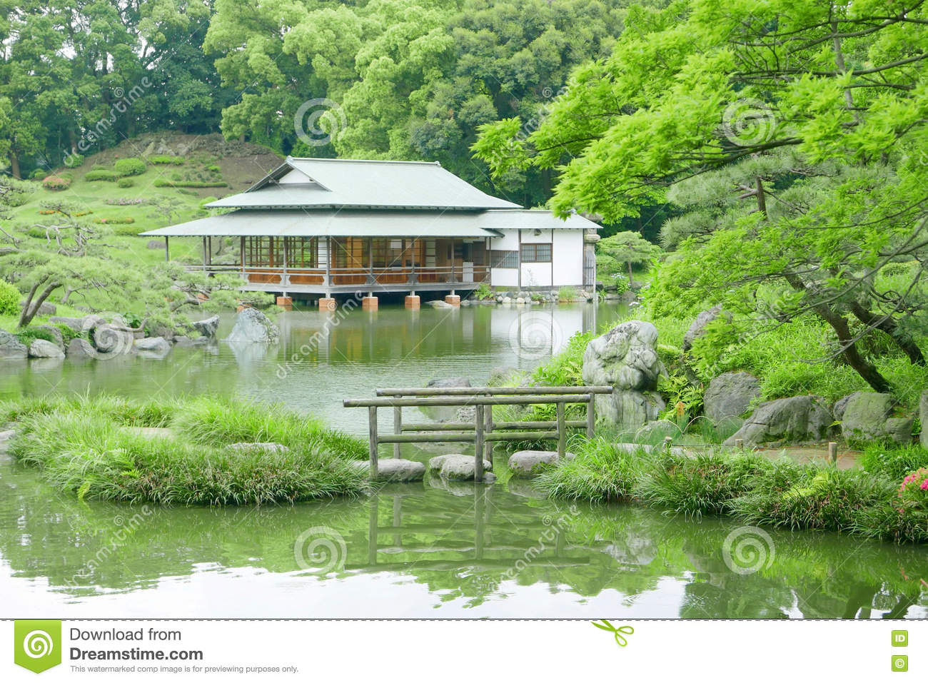 Stone Bridge With Reflection And Pavilion Building In Zen Garden