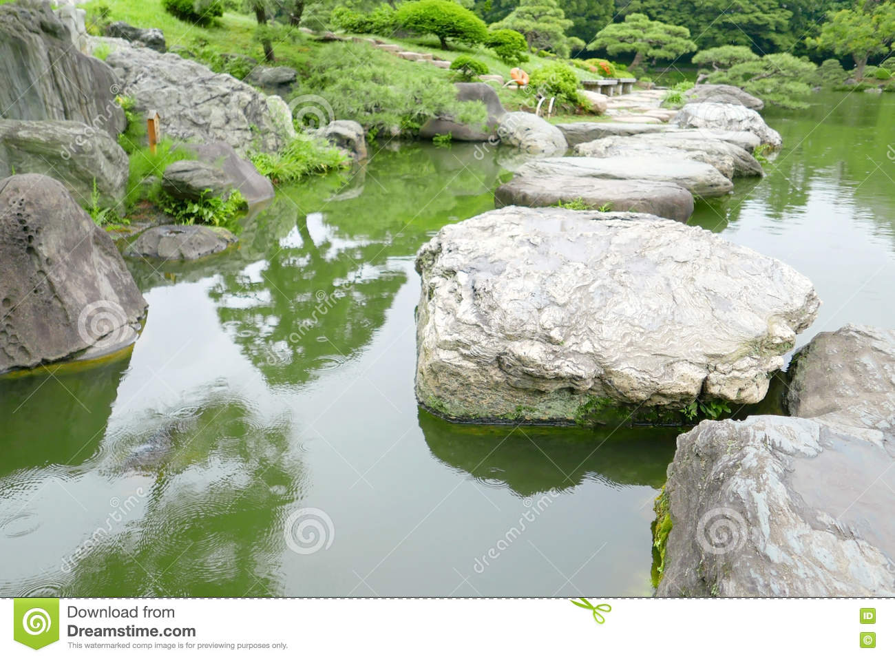 Japanese Garden Stone Bridge stone bridge, water pond in japanese zen garden stock photo