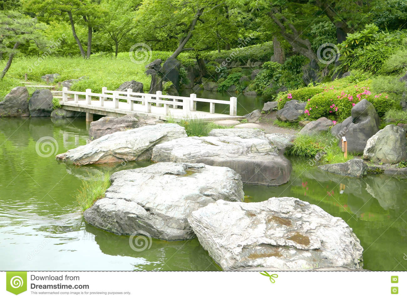 Japanese Garden Stone Bridge stone bridge and water pond in japanese zen garden stock photo