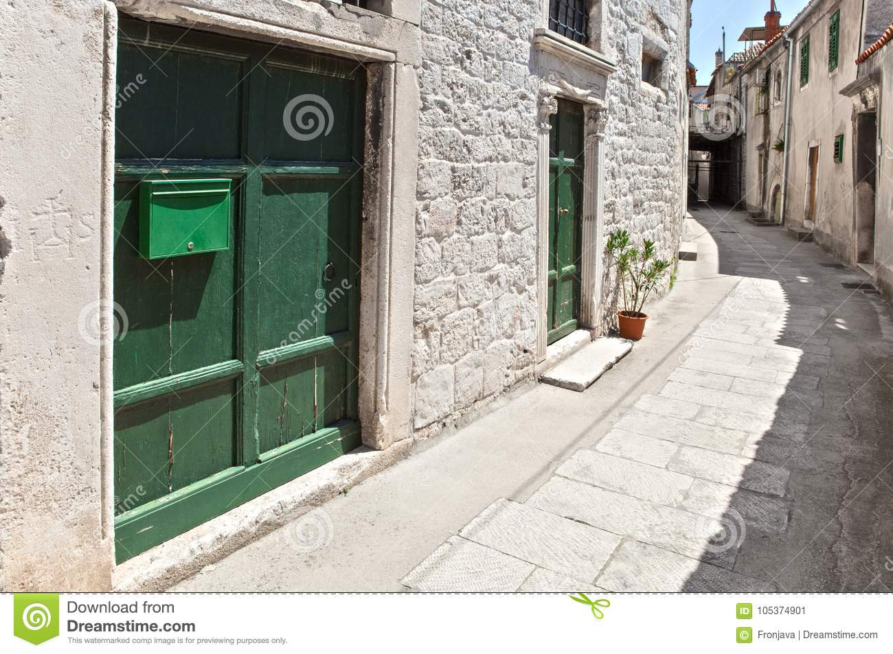 Narrow street in old mediterranean town with green doors on white, stone built facade
