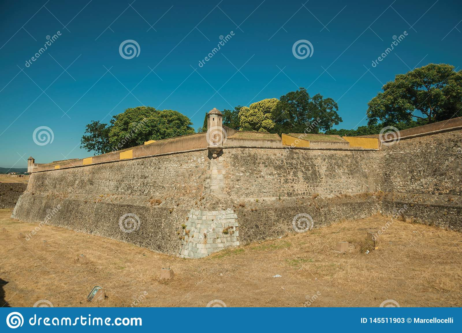 Stone city wall corner with watchtower and dry moat