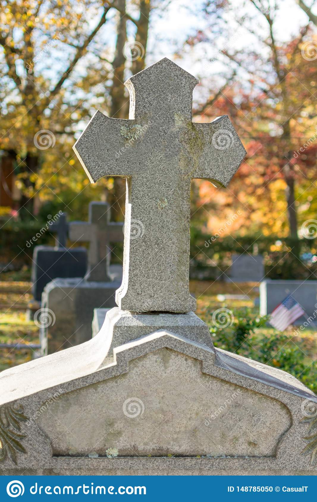 A stone cross atop an unmarked granite headstone at Sleepy Hollow Cemetery, on a calm and quiet autumn afternoon