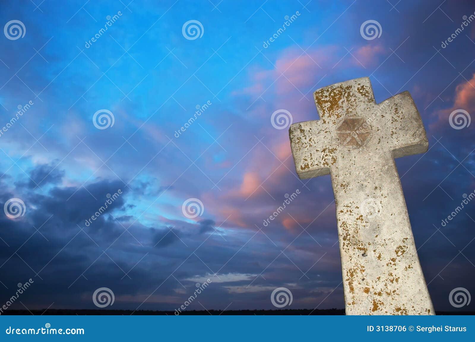 Stone cross on dark sky