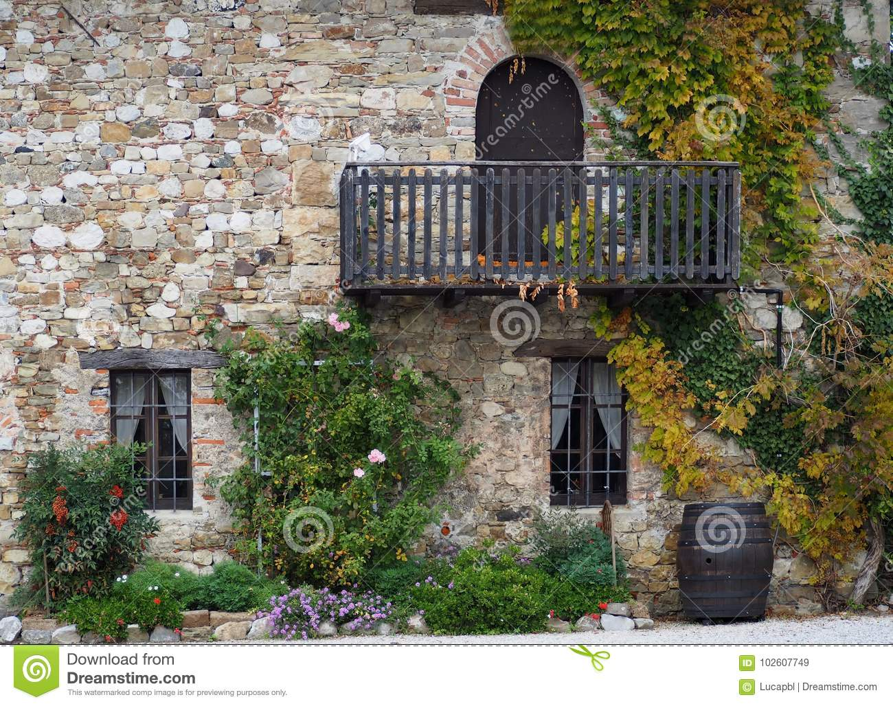 stone facade of an old rural house with wooden balcony and. Black Bedroom Furniture Sets. Home Design Ideas