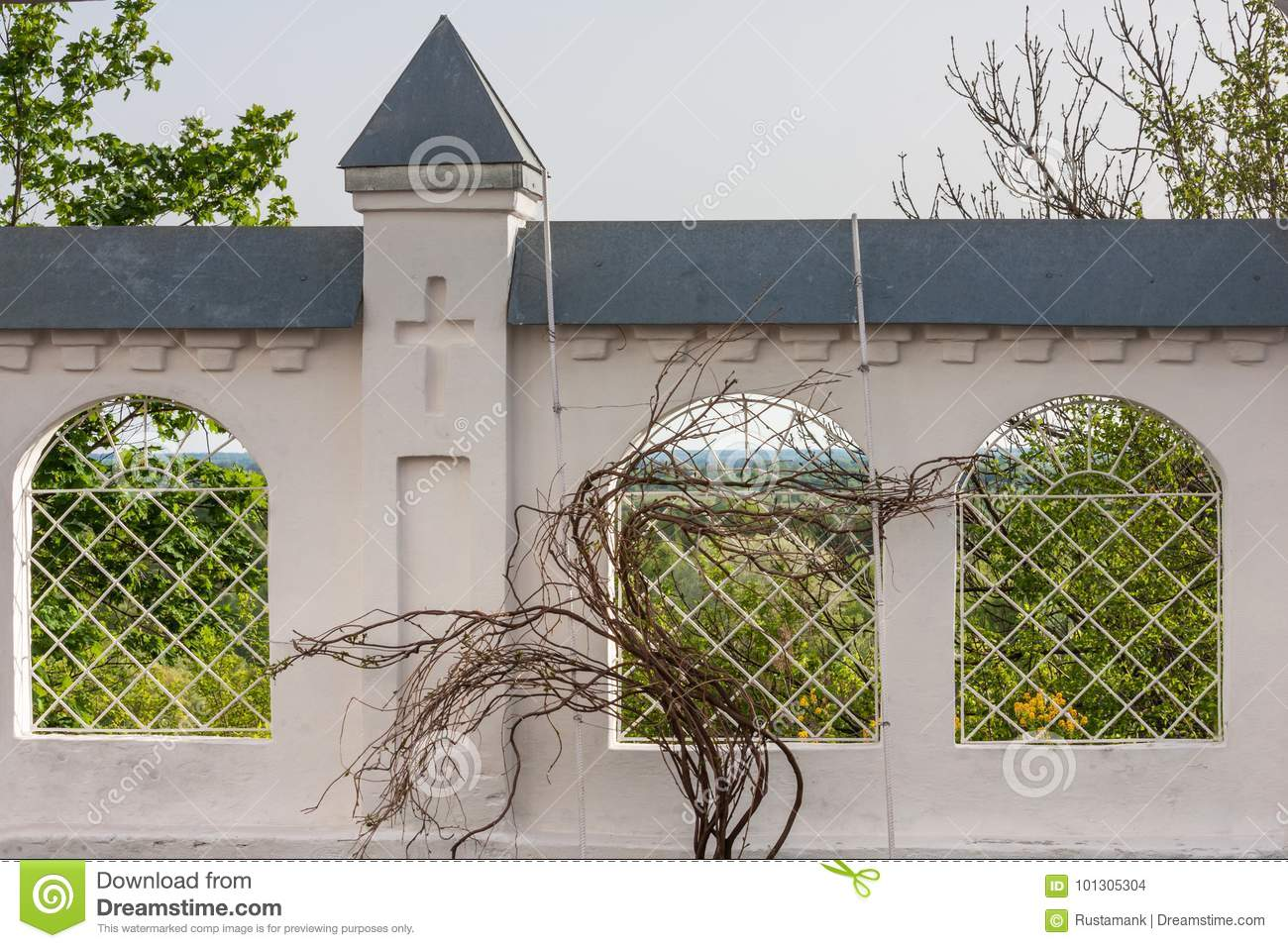 stone fence of an orthodox monastery with lattice windows and a vine