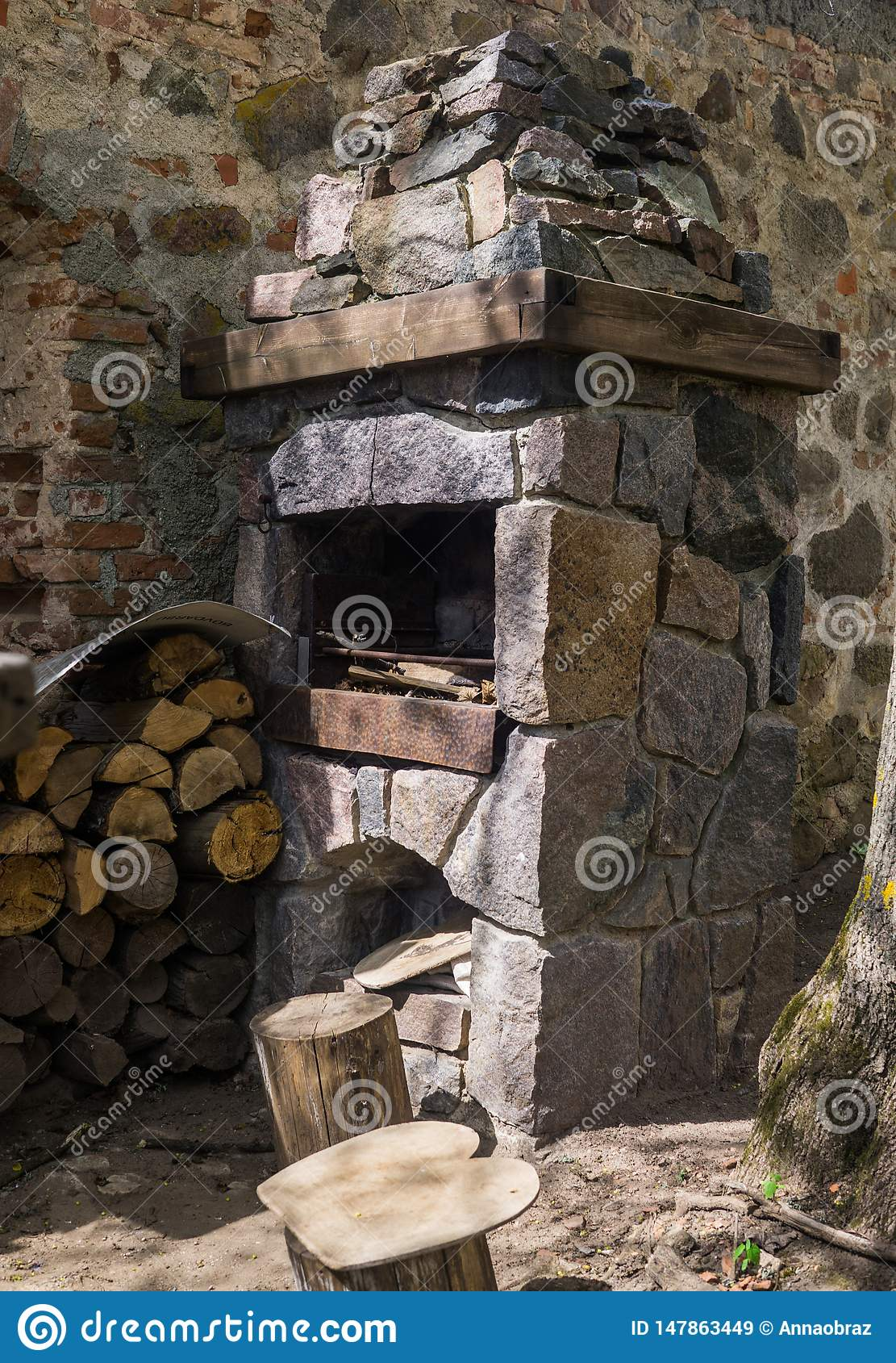 Stone fireplace for frying meat, laid out on the street against the wall, along with firewood