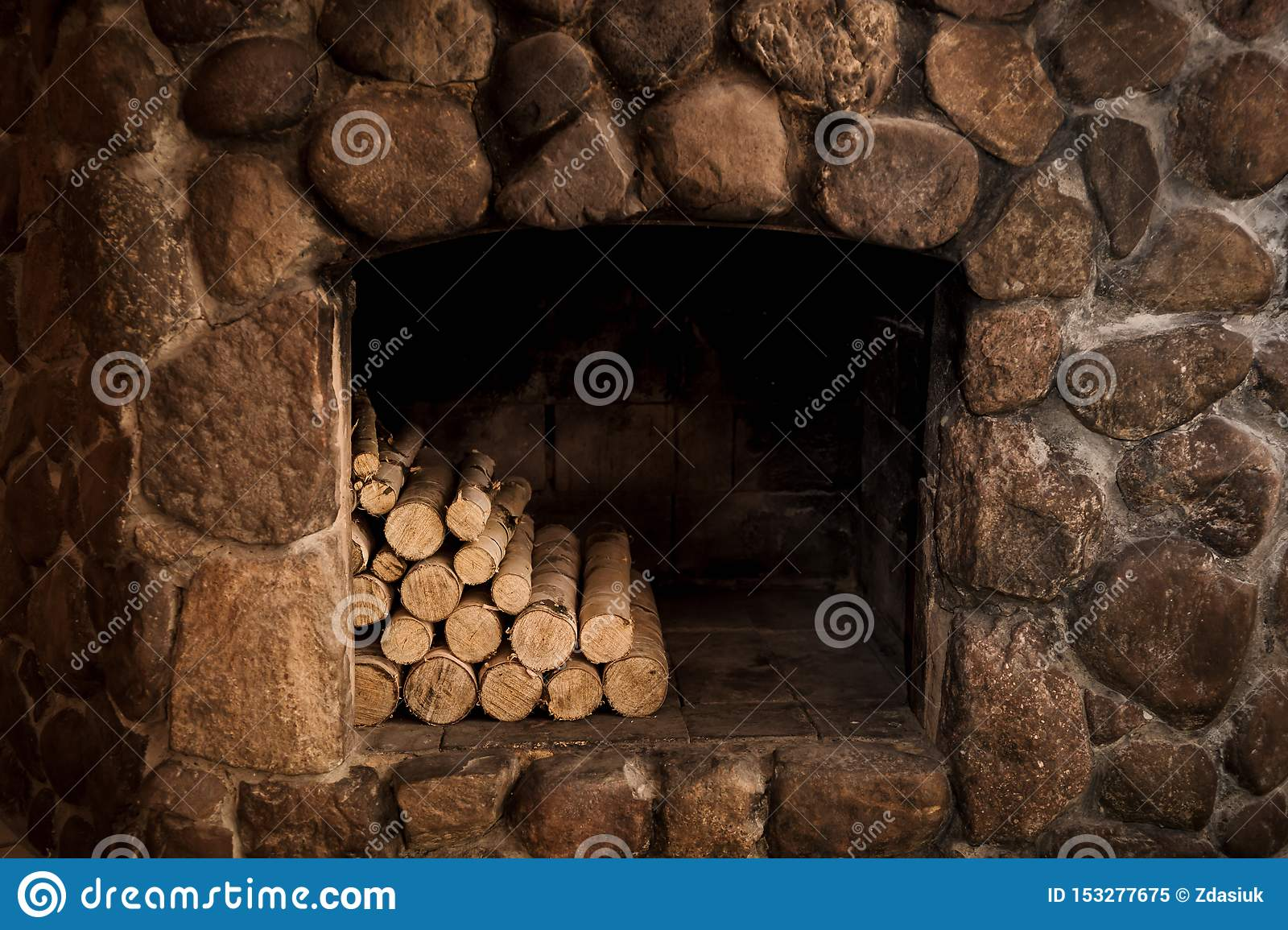 Stone fireplace with hearth and logs